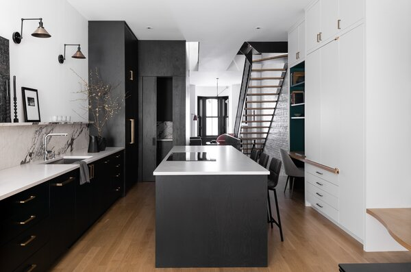 Storage had to be dialed in within the narrow footprint of the brownstone. The black core holds the pantry, while on the right, a bank of custom cabinetry hosts the command station, mop closet, and a concealed bar.-