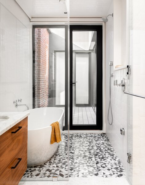 The courtyard extends the sense of space in the main bathroom, and although the latter is in a central location in the narrow building, the courtyard brings in that much more light than is typical in a floorplan like this. The floor tile is the Krista Watterworth Kiss Marble ' tile, and the owners can also open the exterior door there should they want to shower al-fresco.