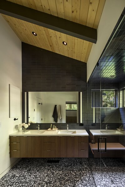 In the main bath, a wall of Heath Ceramics tile joins a terrazzo floor from Ann Sacks.