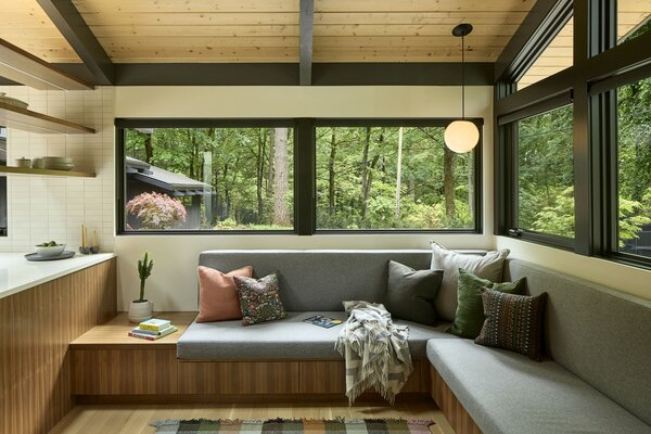 Boyer relocated the laundry room and installed this cozy seating nook for the family in the old space. Occupants can interact with people in the kitchen, or appreciate the views into the front yard and mature trees.