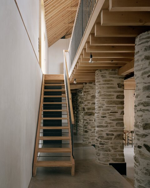 In a lightweight counterpoint to the preserved stone columns, the staircase is composed of floating wood tread and handcrafted metal spindles, fabricated by a local blacksmith.
