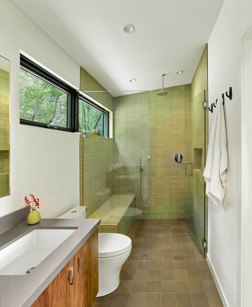 A long, linear window brings light into the Heath Ceramics tile-covered shower, which is curbless, so as to accommodate aging-in-place.