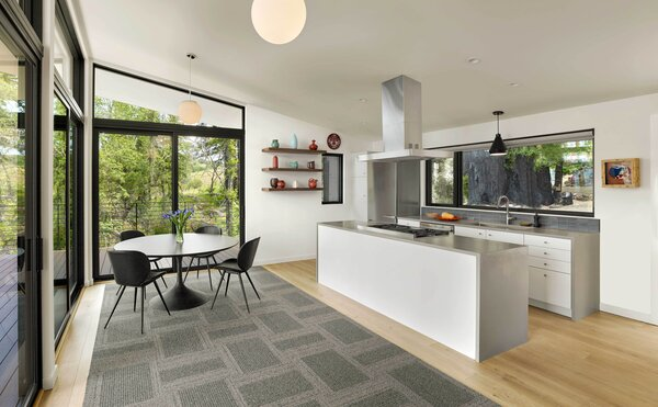 """The kitchen was designed so that the cooktop is in the Caesarstone-wrapped island, which means the cook can enjoy the view while they work. """"I love cooking and looking out,"""" says Michele."""
