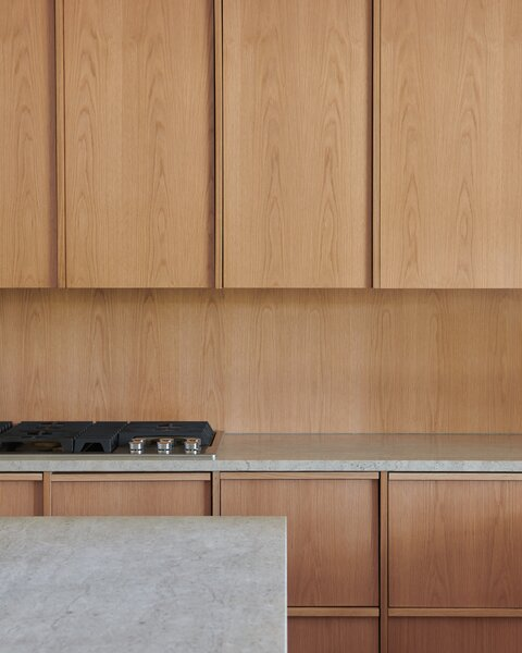 """White oak storage wraps the kitchen, which is tucked under the lower ceiling, to create a more cozy spot that's still connected to the living areas. """"It's such a large space,"""" Erling says of the great room. """"It's nice to be more intimate in the kitchen zone."""" The counters are Gascogne blue limestone."""