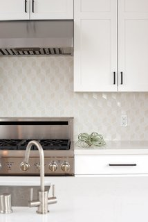 A kitchen is kept light and bright with white cabinets with dark hardware, white countertops, and a geometric patterned backsplash in a range of whites, creams, and beiges from Dwell patterns Heath tile backsplash.