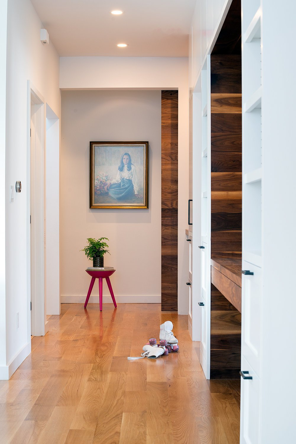 A full wall of built-in storage cabinets accented with walnut and oil-rubbed bronze hardware. A large walnut sliding barn door leads to the master suite and office areas.  Chenery Street Remodel by SF Design Build