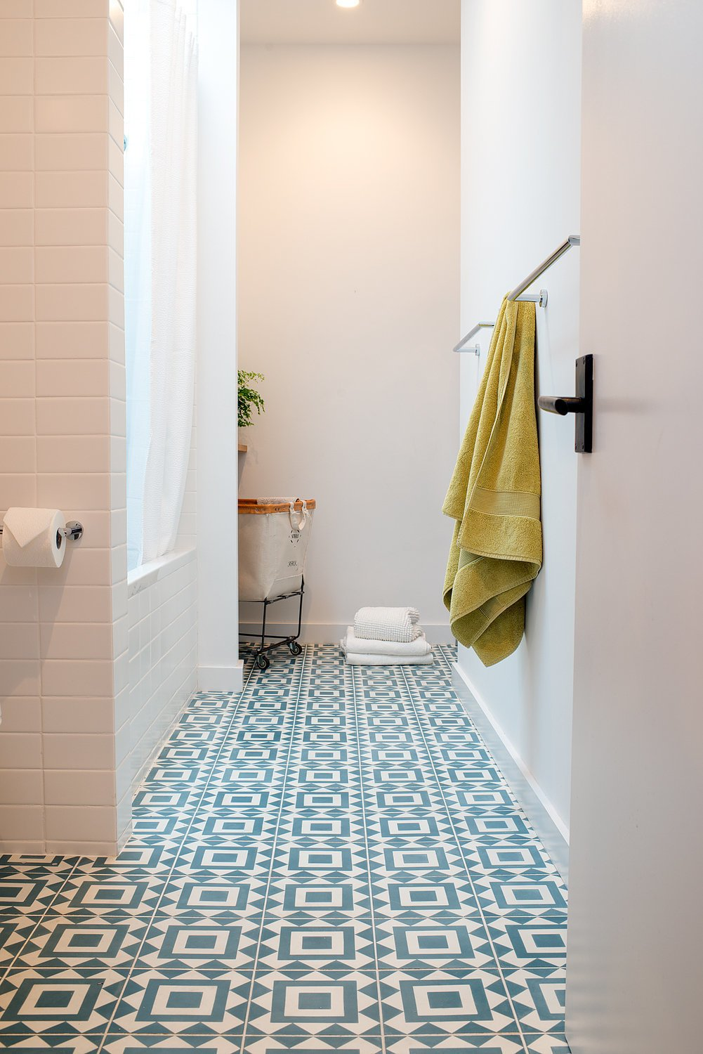 Bath Room, Ceramic Tile Floor, and Subway Tile Wall An existing lightwell was filled-in to create space for a concealed laundry area at the rear of the main bathroom. Soft natural light pours in from the skylight over the tub.  Chenery Street Remodel by SF Design Build