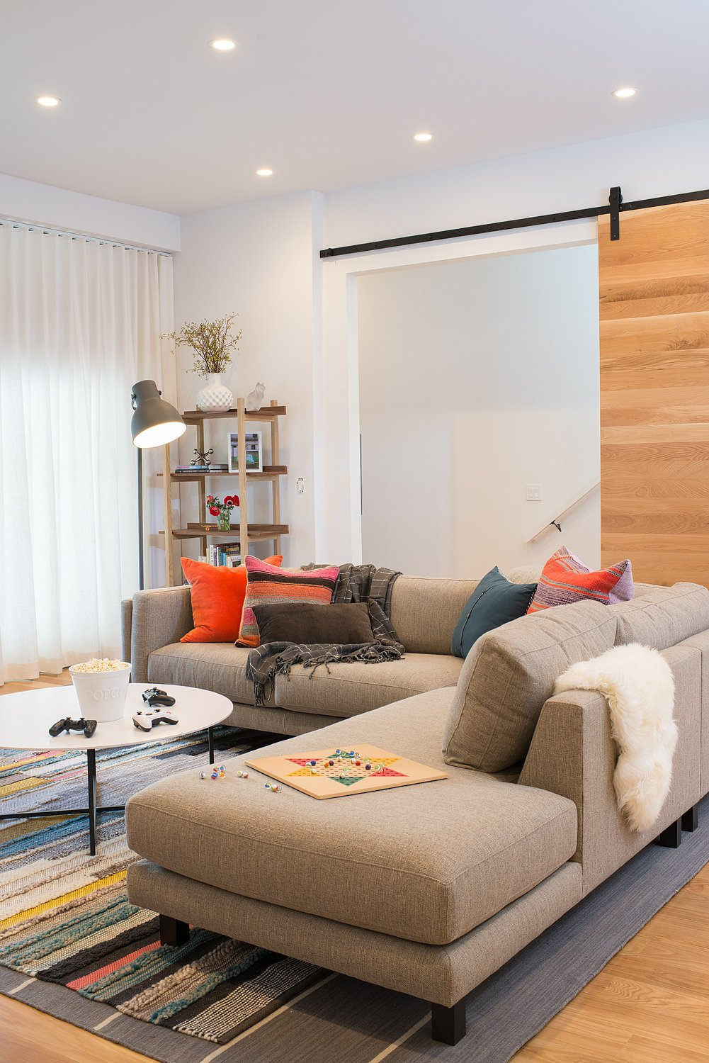 Interior, Doors, Sliding Door Type, and Wood Located on the ground floor, the family room has a large barn door that can be closed to create a guest suite for visitors.  Chenery Street Remodel by SF Design Build