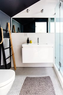 The full bathroom includes Ann Sacks tiles, a wall-hung toilet and a black and white color scheme.