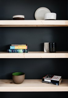 Pine wood shelves that match the flooring with a painted back wall add contrast to the other end of the bedroom.