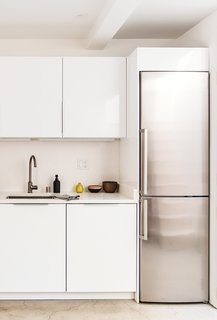 A built-in Liebherr refrigerator pairs well with the bright white cabinets and concrete floors.