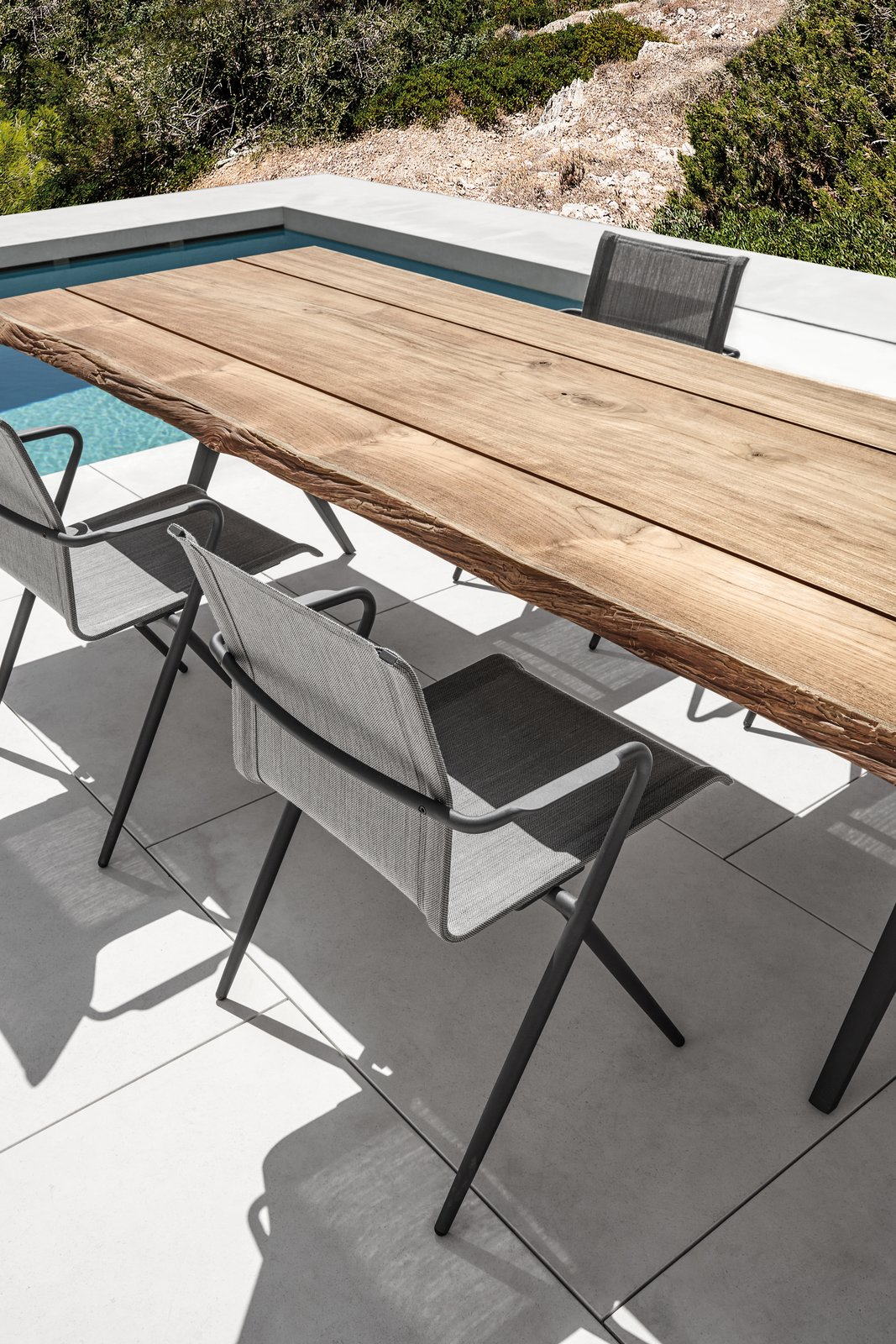 Chair, Table, Outdoor, Large Pools, Tubs, Shower, Small Pools, Tubs, Shower, Swimming Pools, Tubs, Shower, Large Patio, Porch, Deck, Hardscapes, Small Patio, Porch, Deck, Back Yard, and Tile Patio, Porch, Deck Stackable Ryder dining chair in a dark version in contrast to the limited edition teak table Split Raw.  Dining Chairs