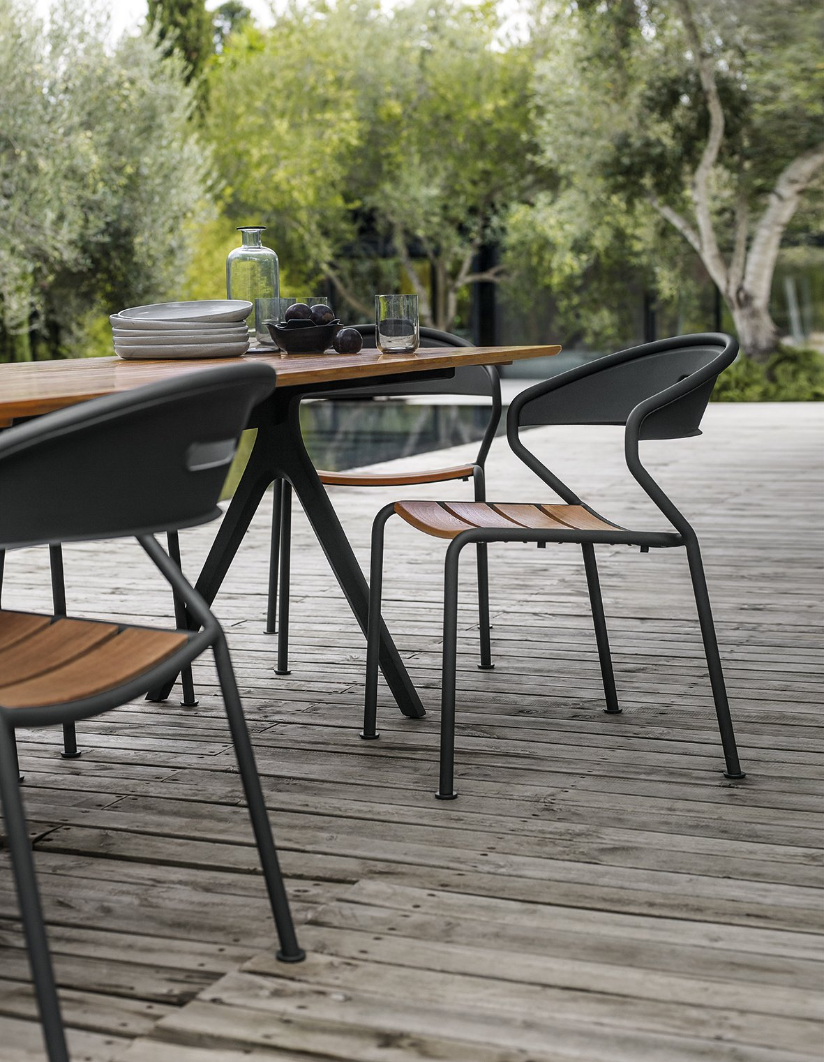 Table, Chair, Outdoor, Large Pools, Tubs, Shower, Large Patio, Porch, Deck, Small Patio, Porch, Deck, Small Pools, Tubs, Shower, Swimming Pools, Tubs, Shower, Wood Patio, Porch, Deck, Trees, Back Yard, and Hardscapes Stackable Curve chair with buffed teak in color Meteor.  Dining Chairs