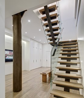 Staircase: View of Lower Level Family Room The biggest single challenge was in the design and fabrication of the staircase.  The stair was required to be both code and child safety compliant.  The staircase's unique features include the co-planar clear-tempered glass-rails and the child-proof open slots under the welded bent steel angles.  Supported by a sizable post concealed in the wall behind the stair, stair attachments are made with moment connections.  All metalwork on this job, including the stairs and door panels were site fabricated forging a unique hand-crafted industrial product, difficult to shop replicate.