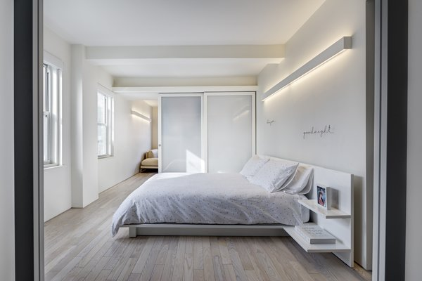 Light Hardwood, Microwave, White, Range Hood, Refrigerator, Range, Dishwasher, Wall Mount, Alcove, Open, Wall, Porcelain Tile, Bedroom, Bed, and Night Stands Master bedroom  Best Bedroom Dishwasher Bed Photos from Studio Combination, Murray Hill, NY