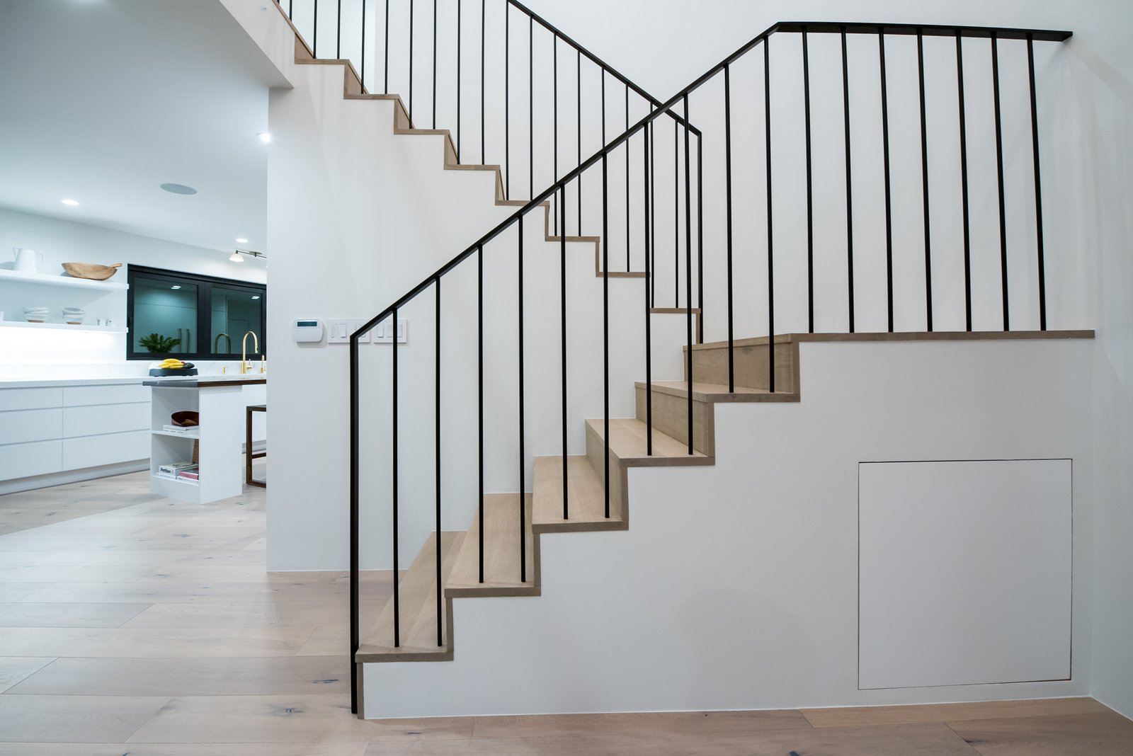 A custom handrail with spindles continuing directly into the treads and landings below allows for a clean minimal look.   The Oaks on Whitman