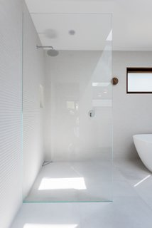 curb-less shower, frame-less glass, textured tile, corner drain