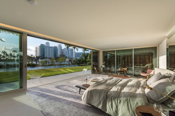 Trees, Sofa, Gardens, Shrubs, Concrete, Chair, Limestone, Stone, Wood, Range Hood, Range, Drop In, Table, Pendant, and Bedroom Floor-to-ceiling sliding glass doors open up to the water in the master bedroom.  Best Bedroom Gardens Range Photos from Pine Tree North