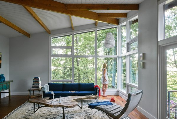 Wood beams radiate from a central structural core to support deep roof eaves, each one painstakingly refinished. New energy-efficient windows create a cozy moment.