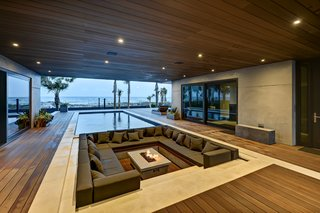 A sunken conversation pit surrounding a fire pit sits adjacent to the pool in this semi-outdoor space at a home in Atlantic Beach, Florida.
