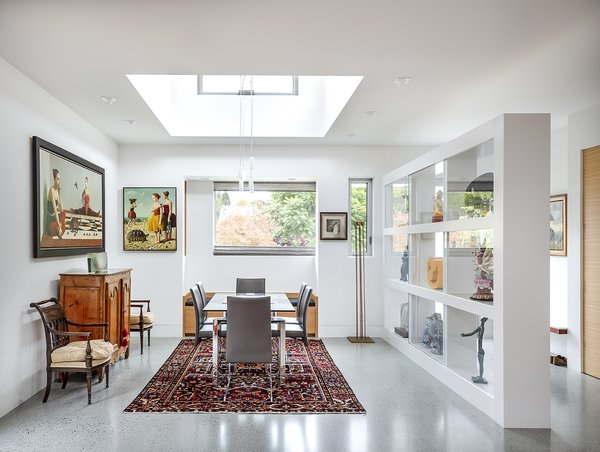 The dining room sits within an open plan, but is defined by a clerestory pop-up and a display wall.