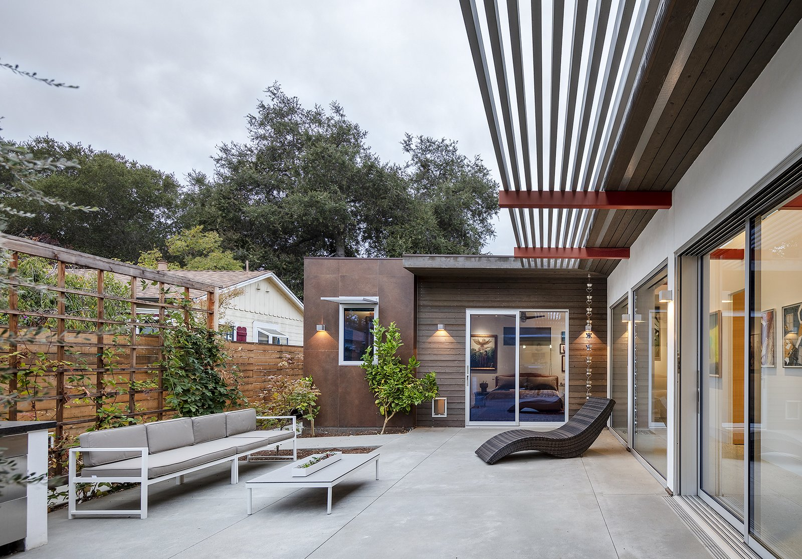Exterior, House Building Type, Flat RoofLine, Wood Siding Material, and Stucco Siding Material The courtyard, approaching dusk  Oak Street by Rossington Architecture