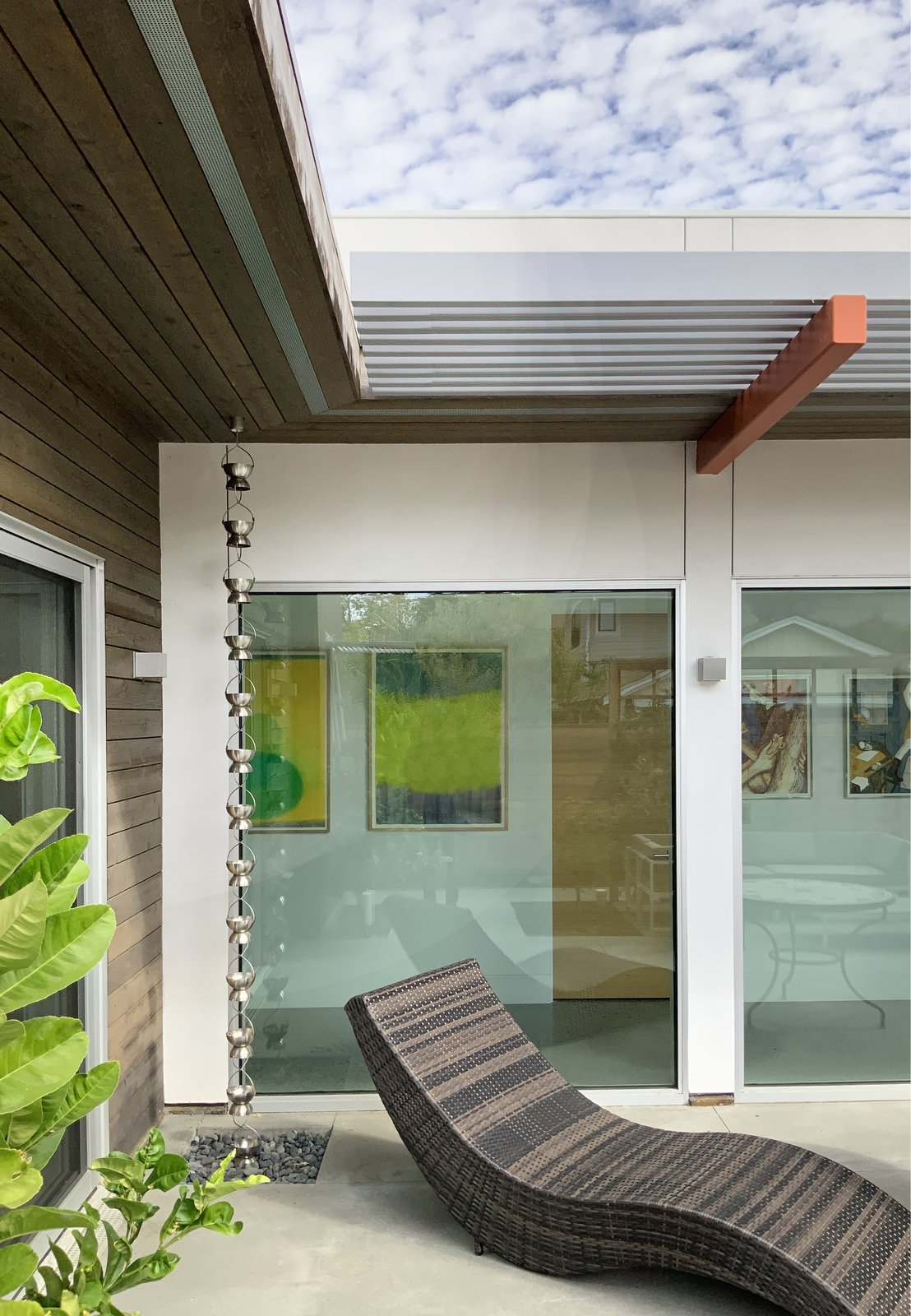 Exterior, House Building Type, Wood Siding Material, Flat RoofLine, and Stucco Siding Material A rain chain directs rainwater to a collection pit. A deep overhang, partly solid and partially open protects the window wall and dapples light across it.  Oak Street by Rossington Architecture