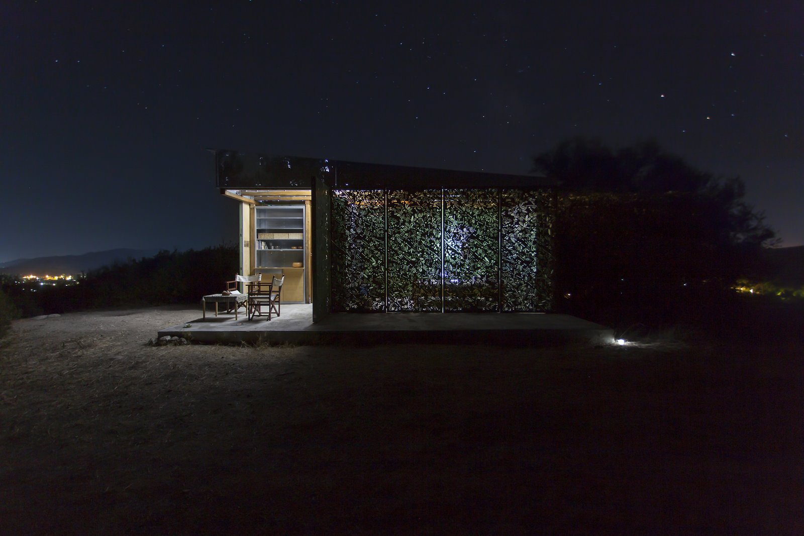 Wood Counter, Wood Cabinet, Concrete Floor, Metal Cabinet, Chair, Coffee Tables, Table, Trees, Shrubs, Small Patio, Porch, Deck, Exterior, Metal, Folding Door Type, Metal Counter, Living Space Room Type, Bed, Accent Lighting, Garden, Desert, and Hardscapes Night view  The Olive Tree House