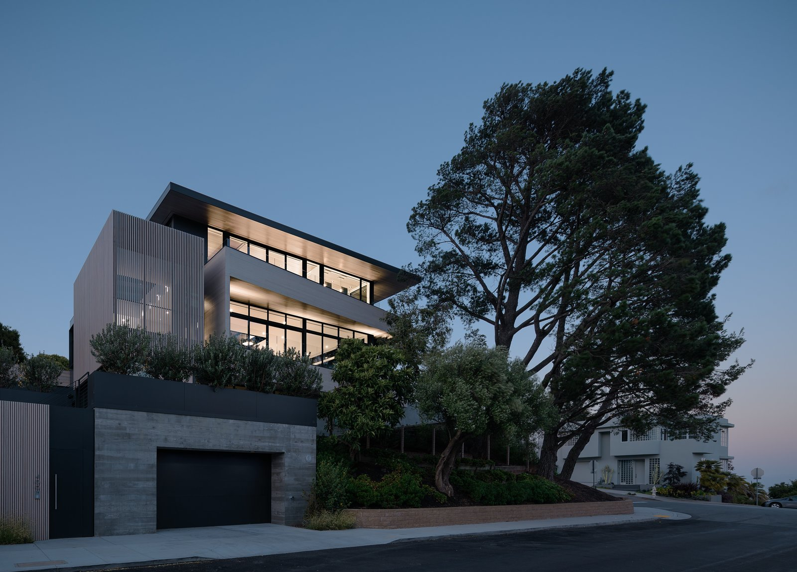 Exterior, Flat RoofLine, House Building Type, Concrete Siding Material, Wood Siding Material, Metal Roof Material, Glass Siding Material, and Metal Siding Material Exterior at Dusk  Photos from Dolores Heights Residence I