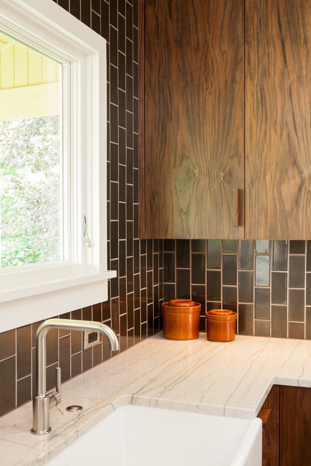 Kitchen, Granite Counter, Ceramic Tile Backsplashe, and Wood Cabinet Walnut + gunmetal: Our goal was to be bold but not cold. Handmade tile adds a humane touch. Richly textured walnut cabinetry and pulls add warmth.  Holly + Magda by Howells Architecture + Design