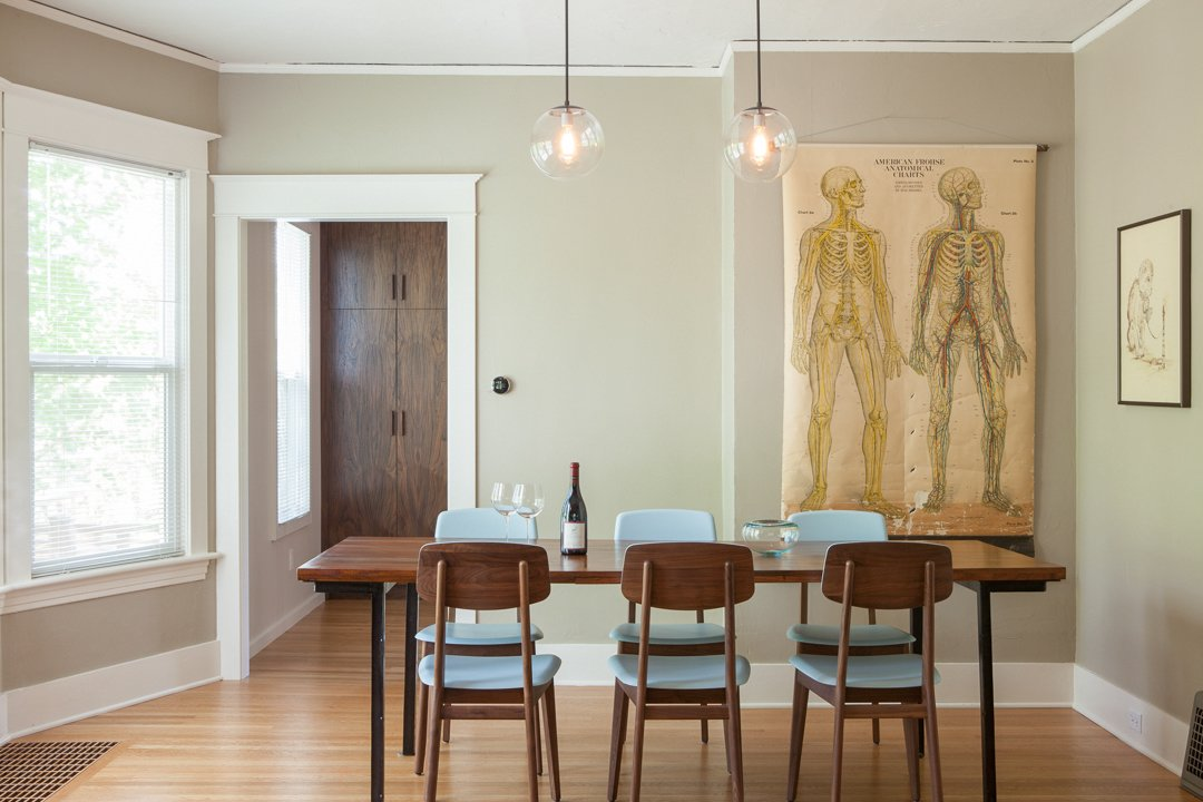 Dining Room The kitchen aesthetic is a counterpoint to the 1909 home. But matched oak flooring and a long-lined, elegant cabinetry scheme seek to harmonize old + new.  Holly + Magda by Howells Architecture + Design