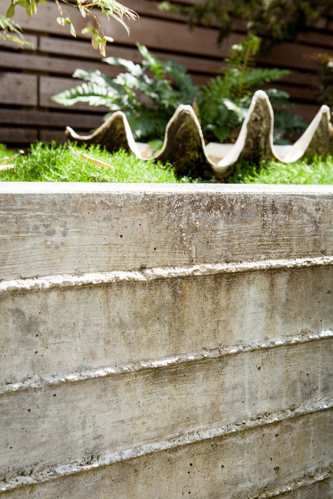 Outdoor, Raised Planters, Concrete Patio, Porch, Deck, Back Yard, Small Patio, Porch, Deck, and Horizontal Fences, Wall Board formed concrete is softened by moss. For more info: https://www.howellsarc.com/projects/michael-b/  Michael B by Howells Architecture + Design