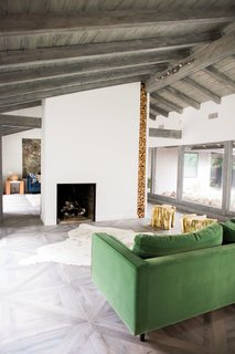 The original fireplace was a rugged rock monolith that extended all the way to the exterior wall and several feet closer to the front windows.  The stone facade was stripped away, which opened up a walkway to the den.  The two-sided fireplace column was wrapped with crisp white drywall.
