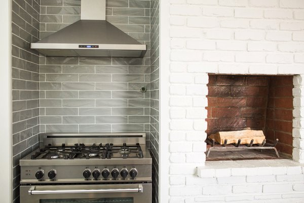 The kitchen fireplace is one of three original to the house, and its traditional staggered brick design became the inspiration for the stagger-set undulating gray porcelain subway tile backsplash.