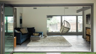 NanaWall bifold glass doors open to the living room and den, allowing views from the back lawn to the front courtyard.