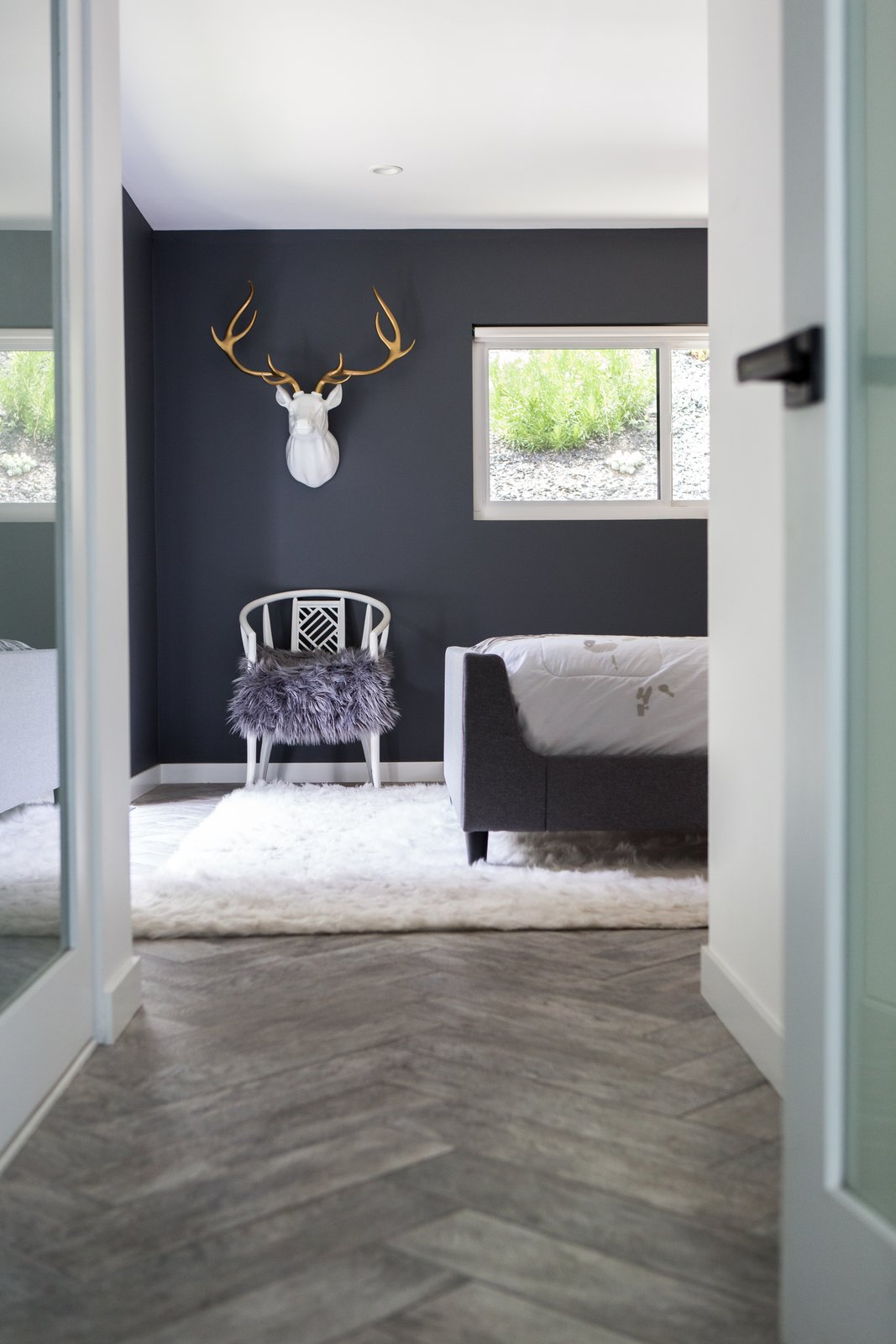 Bedroom, Chair, Bed, Recessed, and Porcelain Tile A gold-antlered ceramic deer head hangs above a flea market Chinoiserie chair in the master bedroom.  Best Bedroom Bed Porcelain Tile Photos from Diablo Ranch