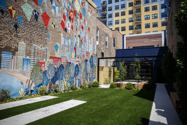 What was once a paved driveway is now a private front courtyard with treads for a car or food truck to pull in, a custom mural created by international artist, David Fleck, landscaping by Reveal Design, turf for low maintenance!