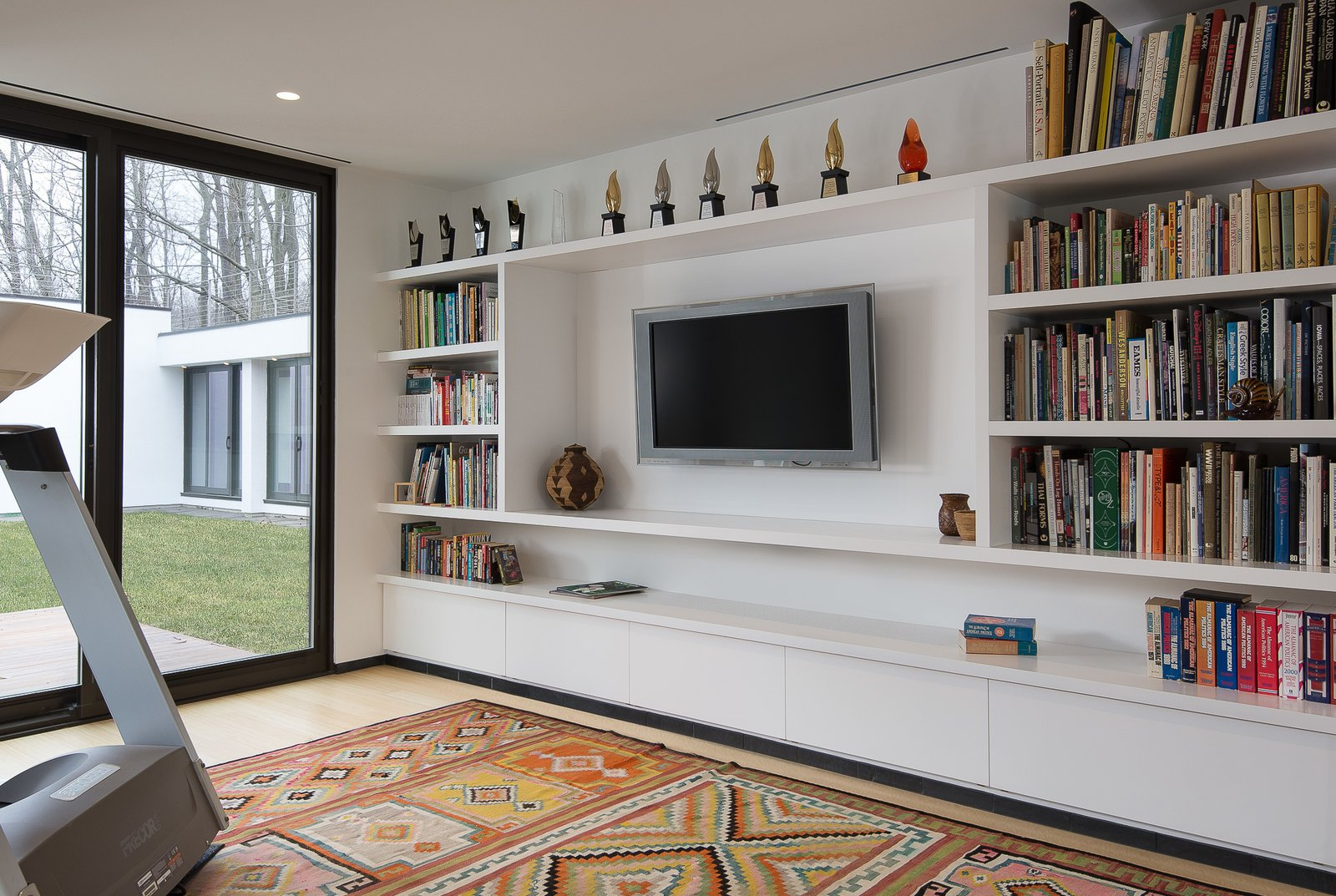 Office, Library Room Type, Bookcase, Storage, Study Room Type, Shelves, and Light Hardwood Floor Library / exercise room  House in the Woods by Kim Smith