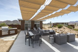 Owner Dave McAdam started Blue Sky Building Systems, whose steel-frame system easily adapts to sloped lots, before founding Homestead Modern, whose pre-designed homes can be built nearly anywhere for a set price. Above, a shaded patio off the main house enjoys access to a fire pit and a grill.