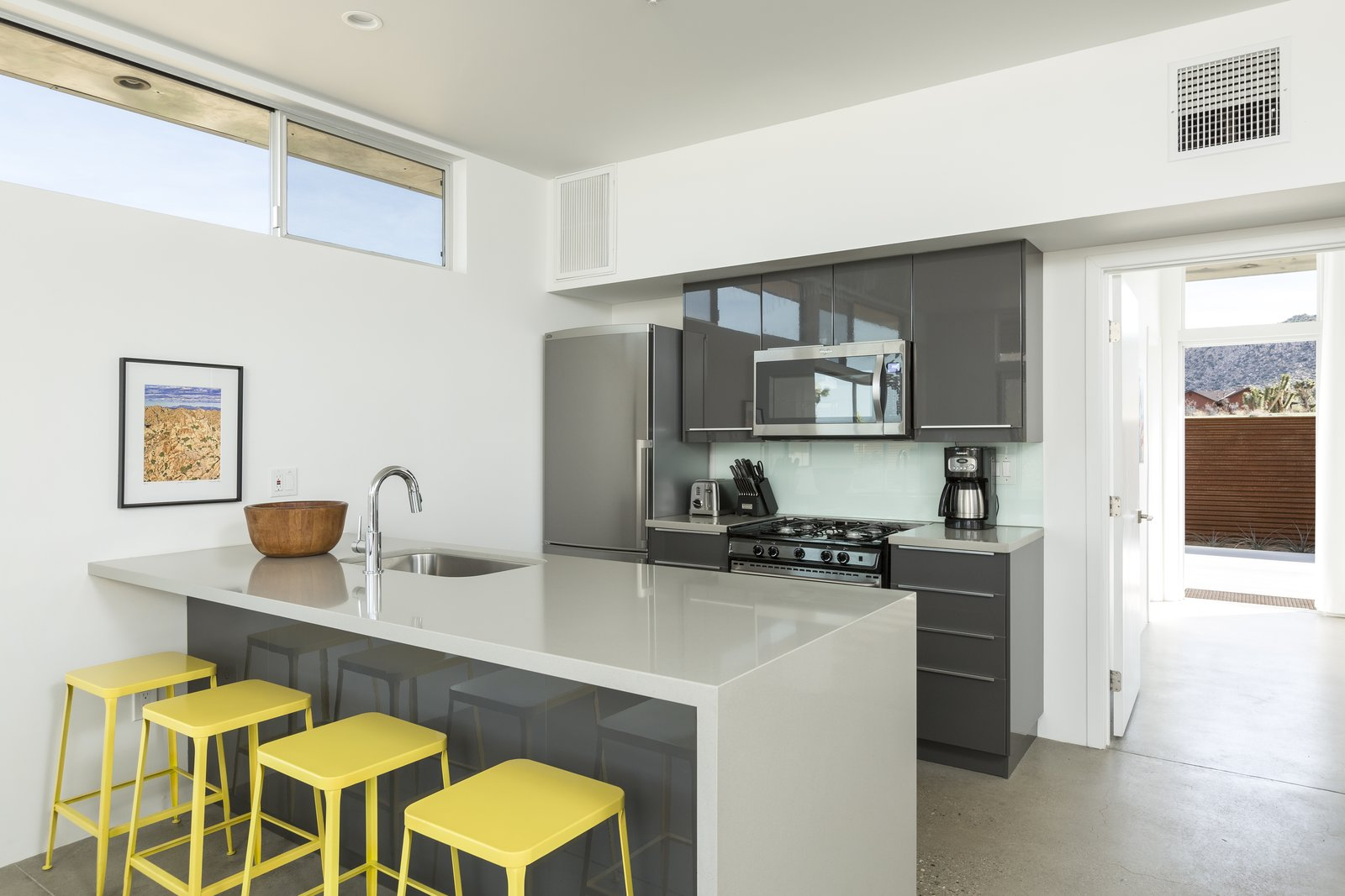 Kitchen, Concrete Floor, Refrigerator, Recessed Lighting, Microwave, Range, Wall Oven, and Undermount Sink Sleek, modern kitchen area of the main home  Photo 4 of 10 in This Modern Homestead With a Vintage Trailer Offers Adventure in California's High Desert
