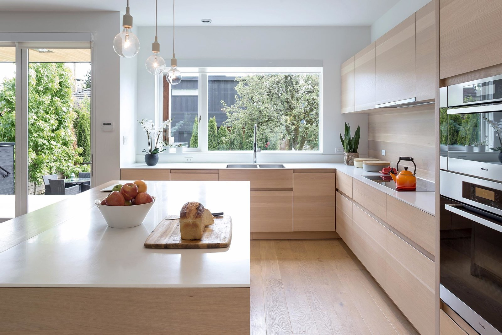 Kitchen, Engineered Quartz, Wood, Light Hardwood, Pendant, Wood, Recessed, Wall Oven, Range, Microwave, and Undermount Alternate view of kitchen which shows custom millwork and continuous wood backsplash which creates an effortlessly seamless effect.  Best Kitchen Wall Oven Wood Undermount Recessed Engineered Quartz Light Hardwood Photos from Custom Millwork and Bright Interiors Star in an Elegant Vancouver Home
