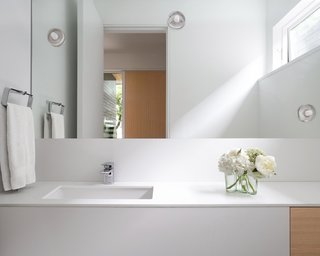 Bathroom palette blends seamlessly into the whole floor plan with white oak accents and decorative lighting.