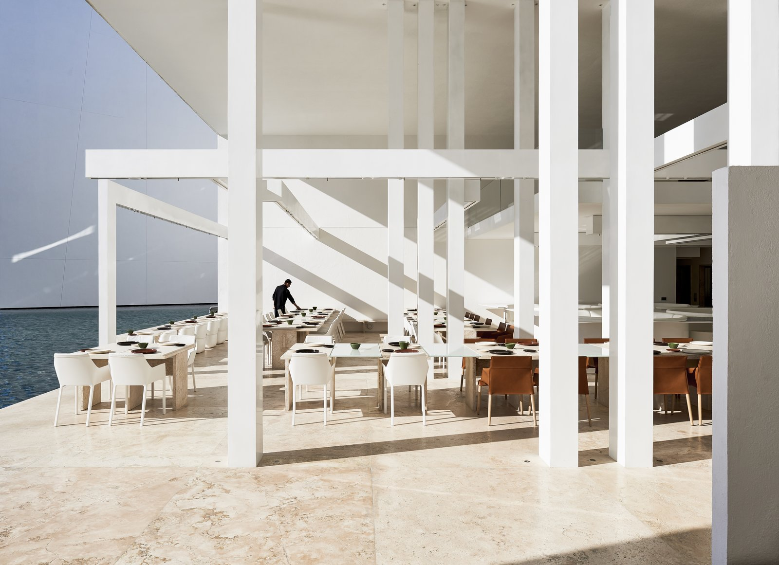 Desert, Large Patio, Porch, Deck, Dining Room, Travertine Floor, Chair, and Table With white travertine floors and muted, modern furnishings by Poliform, this restaurant at the resort is all about the view of the ocean and the sensoral connectivity to it.  Photo 2 of 12 in An Exquisite Beach Resort on Baja California Sur Lies Where the Water Meets the Horizon