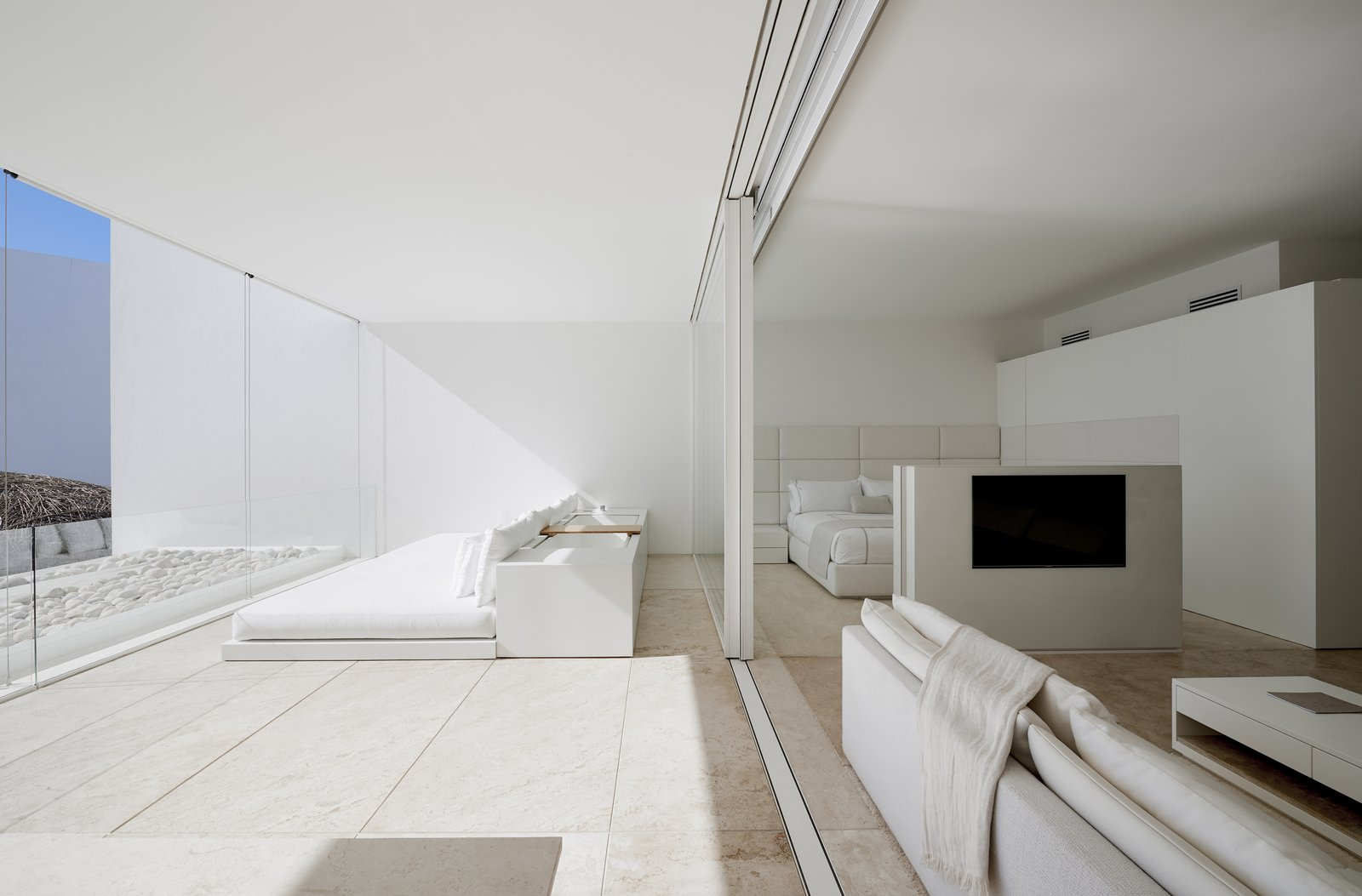 Travertine Floor, Bed, Storage, Living Room, Media Cabinet, Sofa, and Coffee Tables The simplistic, muted interiors balance with the minimal architecture.  Photo 8 of 12 in An Exquisite Beach Resort on Baja California Sur Lies Where the Water Meets the Horizon