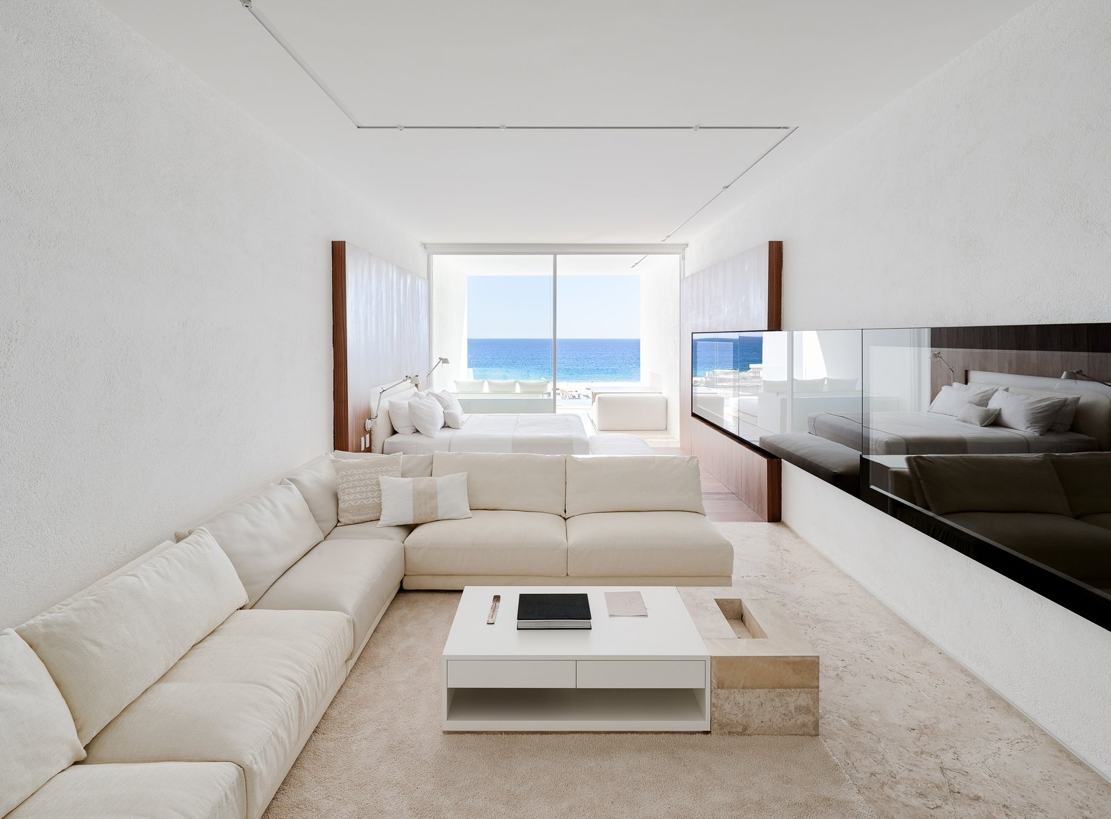 Bed, Living Room, Medium Hardwood Floor, Carpet Floor, Sectional, and Coffee Tables White travertine floors, neutral furnishings, and soft wood tones keep the emphasis on nature, the view, and the sensory experience of being on the ocean.  Photo 10 of 12 in An Exquisite Beach Resort on Baja California Sur Lies Where the Water Meets the Horizon