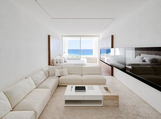 White travertine floors, neutral furnishings, and soft wood tones keep the emphasis on nature, the view, and the sensory experience of being on the ocean.