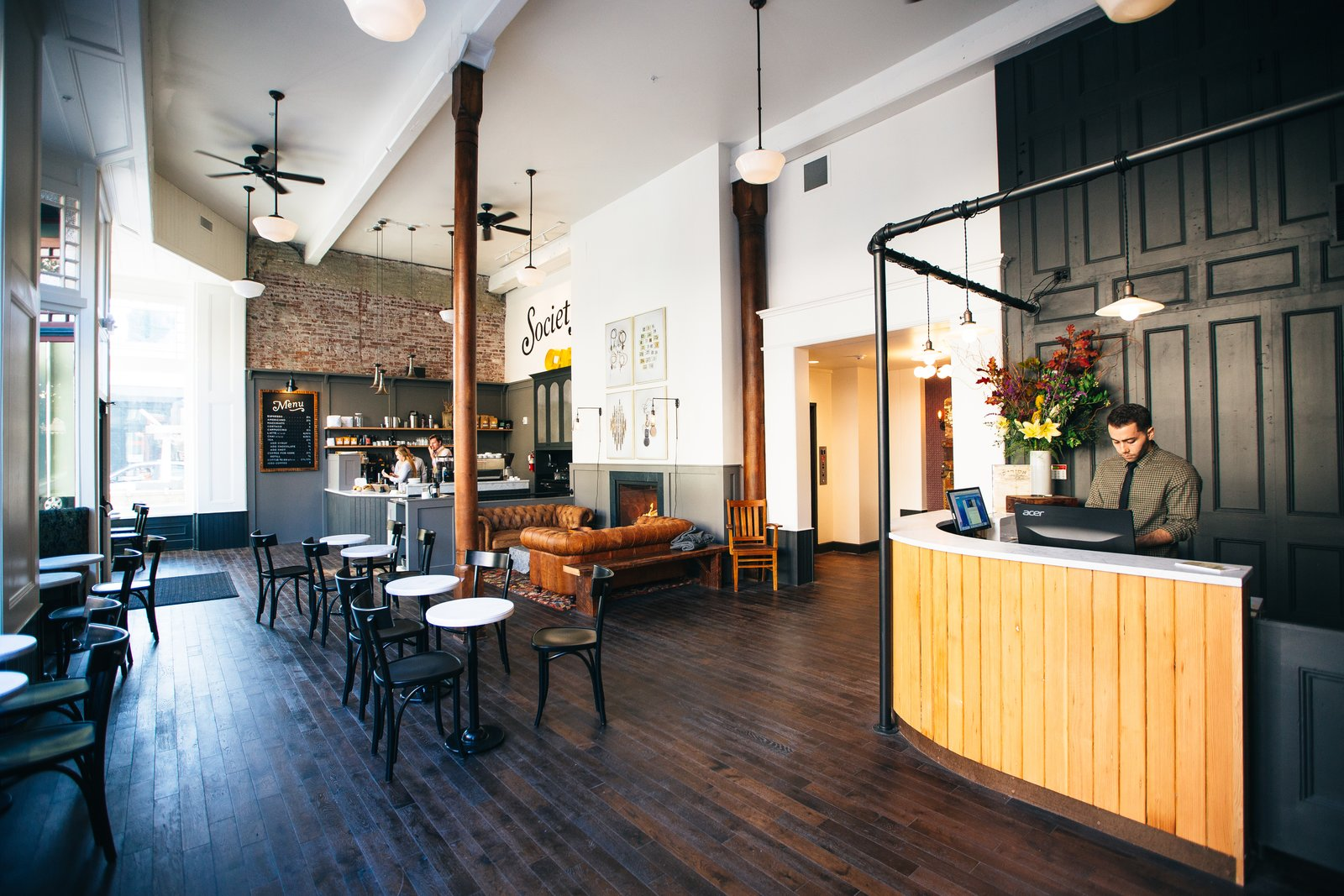 Table, Pendant Lighting, Chair, Dark Hardwood Floor, Living Room, Sofa, Wall Lighting, and Gas Burning Fireplace The lobby of the hotel contains a cafe and lounge space complete with a fireplace.  Photo 4 of 11 in A Chic Portland Hotel Offers Lodging As Affordable as $35 a Night