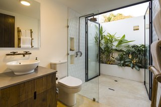 An outdoor shower accessed from the interior bath provides a private retreat under the sun and sky of the landscape.