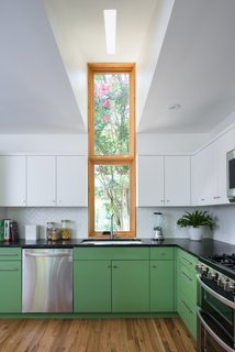 A tall, slender window in front of the sink creates a built in light well, allowing daylight to reflect further inward.