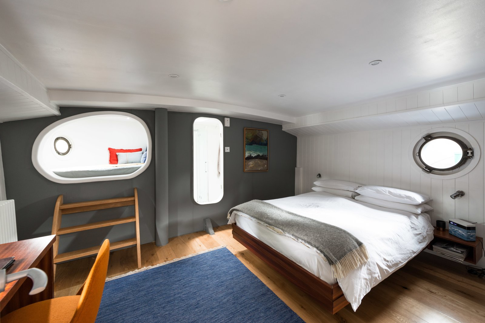 Bedroom, Bed, Wall Lighting, Light Hardwood Floor, and Rug Floor The Master Bedroom includes a private en-suite, desk, and  Photo 7 of 9 in Londoners Can Live in This Scandinavian-Inspired, Converted Barge For $424K
